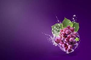 Water splashing on fresh red grapes