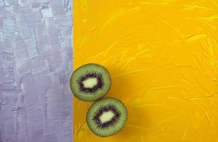 Top view of sliced kiwi on colorful surface