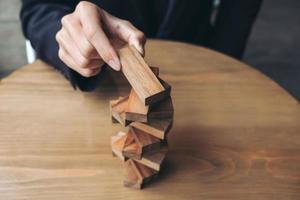 Mano del empresario colocando y tirando de un bloque de madera en la torre