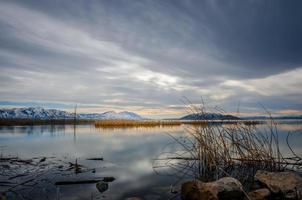 Lake near mountains at dusk photo