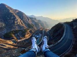 View of person's feet hanging out towards cliff photo