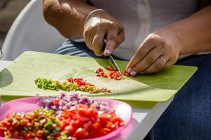 Person chopping vegetables on green cutting board