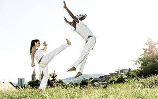 par de artistas de capoeira haciendo patadas foto