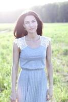 Woman in a dress standing in a field photo