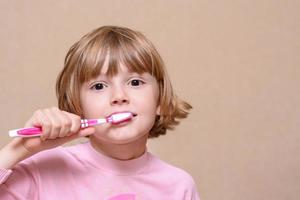Girl brushing her teeth with a toothbrush photo