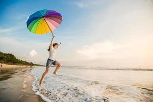 Cheerful young girl with rainbow umbrella having fun on the