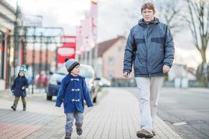 Father and two little sibling boys walking on the street photo