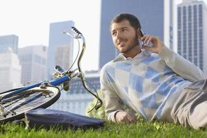 empresario mediante teléfono móvil en bicicleta en el parque foto
