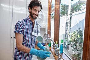 Bearded man washing dishes in a sink with gloves on photo