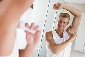 Hombre en el baño aplicando desodorante sonriendo foto