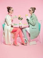 Two girls blonde hair fifties fashion style drinking tea. photo