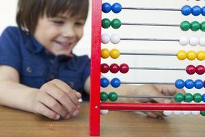 niño sonriente jugando con ábaco