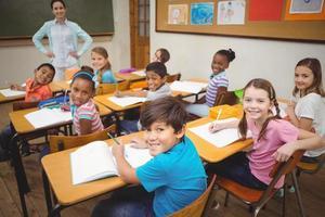 Alumnos sonriendo a la cámara durante la clase.