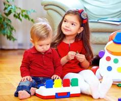 cute babies playing toys at home photo
