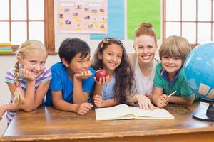 Cute pupils and teacher smiling at camera in classroom