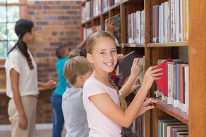 Cute pupils and teacher looking for books in library