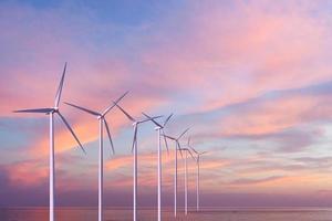 Wind generators turbines in the sea on sunset photo