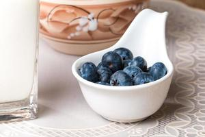 blueberries and milk products on wooden table