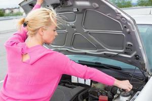mulher inspecionando o motor do carro quebrado.