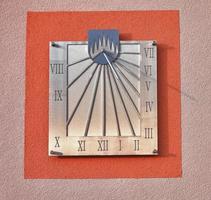 Sundial on facade of  house photo