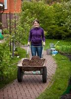 smiling woman carrying garden wheelbarrow