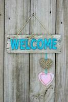 Welcome sign with hearts hanging on wood background
