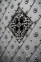Old richly decorated iron door with grille