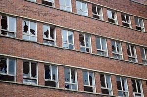 Fachada de ventanas rotas en edificio de ladrillo foto