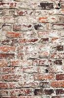 Old uneven decayed whitewashed shabby brick wall