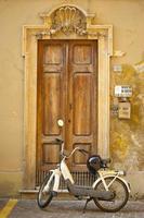 Motorcycle parked in front of wooden door photo