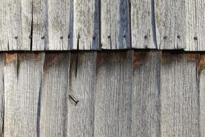 weathered wooden barn - facade shingles in sunlight