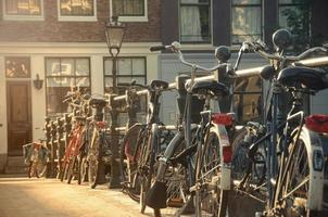 Bicyles against a bridge guardrail in Amsterdam, Netherlands photo