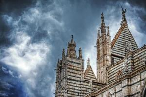 Siena Duomo under a dramatic sky seen from behind