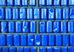 Wall of blue painted used metal cans background photo