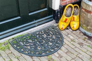 Wooden shoes and doormat at door of old Dutch house