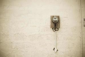 bare wall with electric meter; sepia toned photo