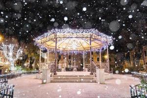 Gazebo en una plaza del pueblo iluminado festivamente para Navidad