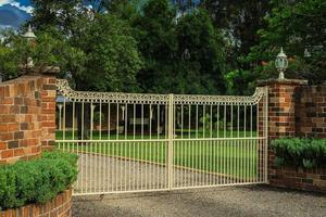 Metal driveway entrance gates set in brick fence photo