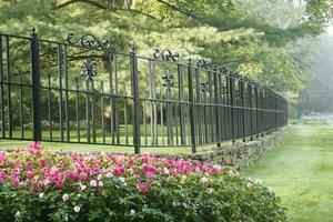 Valla de hierro de estilo francés con flores impatiens foto
