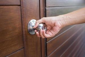 Person grabbing a silver door knob on wooden door photo