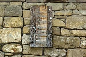 Vintage Wooden Signboard on Old Stone Wall photo