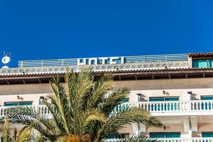 Fachada junto al mar de un hotel de playa en Mallorca con palmeras foto