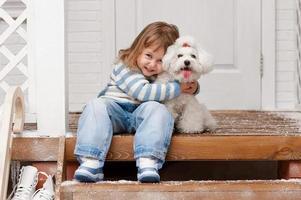 niña con un perro en el porche delantero foto