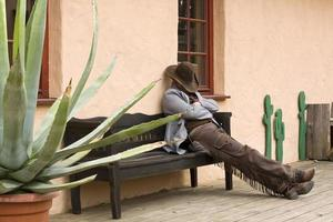 Cowboy resting on bench