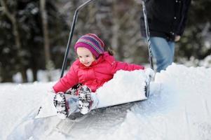 Winter fun: having a ride on snow shovel
