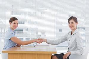 La empresaria un apretón de manos con el entrevistado y ambos sonriendo a la cámara foto