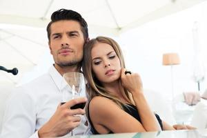 Couple sitting with glass of wine photo