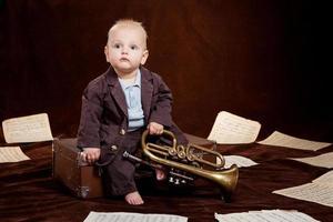 Baby Boy caucásico juega con trompeta entre hojas con musica