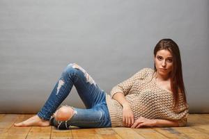 Brunette woman lying on wooden floor