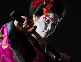 Geisha pulls out sword of sheath on black